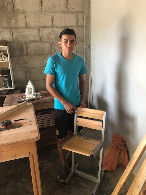 Josue proudly displays a chair he made in his woodworking classes.
